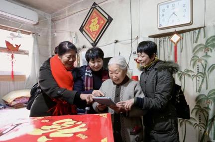 2018年春节前,房泽秋(左二)与志愿者走访看望90岁的朱大娘。 (央视网记者  李文亮 摄)