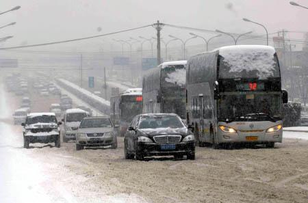 Cars move slowly on the Third Ring Road in Beijing, China, Jan. 3, 2010. Heavy snow hit Beijing on Sunday to close expressways, delay flights and disrupt bus services. (Xinhua/Tang Zhaoming)