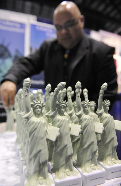 Figurines of the Statue of Liberty are shown during the 2010 International POW WOW at the Orange County Convention Center in Orlando, Florida, the United States, May 17, 2010. The U.S. Travel Association's International POW WOW, the travel industry's premier international marketplace and the largest generator of visit USA travel, opened here on Monday. U.S. travel organizations and foreign business agents will conduct business negotiations during the exhibition. (Xinhua/Zhang Jun)