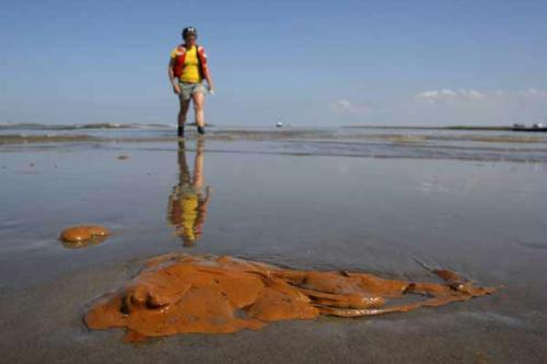 Greenpeace volunteer Lauren Valle walks along a sandy beach on the east bank of the Mississippi River where it meets the Gulf of Mexico as globs of oil wash up on shore in Louisiana May 17, 2010. (Xinhua/Reuters Photo)
