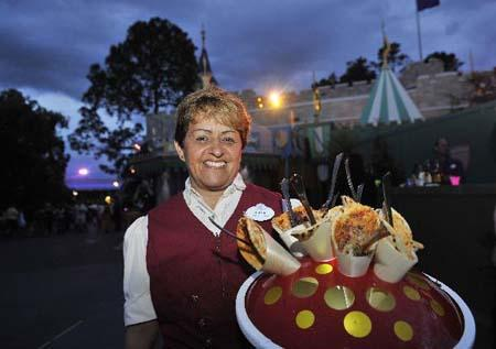 A staff member presents food at Disney's Magic Kingdom Park during a welcome event prior to the 2010 International POW WOW in Orlando, Florida, the United States, May 16, 2010. The annual premier international marketplace for travel to the United States, will gather over 1,000 U.S. travel organizations and worldwide tourism operators. [Xinhua photo]