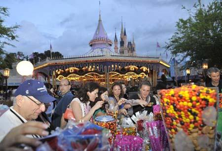 People try candies at Disney's Magic Kingdom Park, during a welcome event prior to the 2010 International POW WOW in Orlando, Florida, the United States, May 16, 2010. The annual premier international marketplace for travel to the United States, will gather over 1,000 U.S. travel organizations and worldwide tourism operators. [Xinhua photo]
