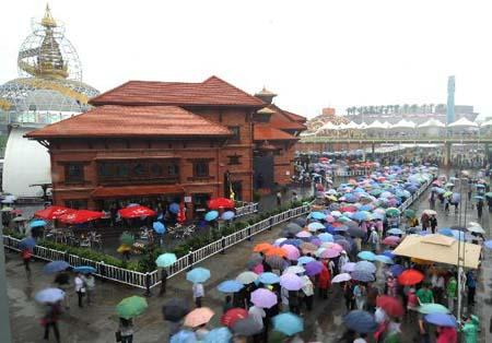 People visit the 2010 World Expo in rain in Shanghai, east China, May 22, 2010. Some 356,500 people visited the World Expo on Saturday despite the drizzle, setting a new record of the daily number of visitors since the Expo opened on May 1, according to official statistics. (Xinhua photo)