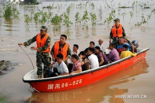Fire fighters help the trapped villagers evacuate to safe places in Fuzhou City, east China's Jiangxi Province, June 22, 2010. The heavy rains and floods ravaging 10 southern Chinese provinces had killed 199 and left 123 missing as of Tuesday, according to the Ministry of Civil Affairs.(Xinhua/Zhou Ke)