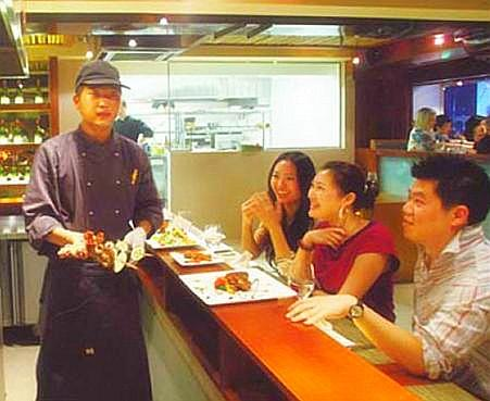Waiter serves grilled kebabs to diners.