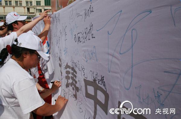 """心脑血管医务专家在""""共铸中国心""""爱心横幅上签名留念。"""