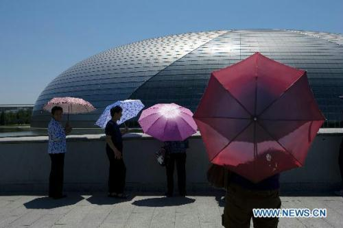 Tourists visit the National Centre for the Performing Arts in Beijing, capital of China, on July 6, 2010. The temperature in Beijing reached 41.8 degrees Celsius on Tuesday.(Xinhua/Shen Bohan)