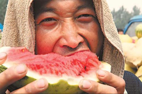 AwatermelonvendorbitesintooneofhisfruitstobeattheheatatavegetablemarketinBozhou,Anhuiprovince,onTuesday,whenthetemperaturesoaredtoabove35C.(Source:ChinaDaily)