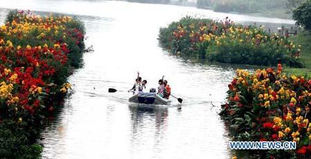 ExcursionistsrevelinboatingalongtheflowerybrookletontheupperreachesofBaiheRiver,withover800,000squaremetersofflowersandplantsgrowingonthewatersurfacethathaveremarkablybeautifiedtheecologicalambienceandmadeitantouristattractioninShuangliuCounty,southwestChina'sSichuanProvince,July7,2010.(Xinhua)