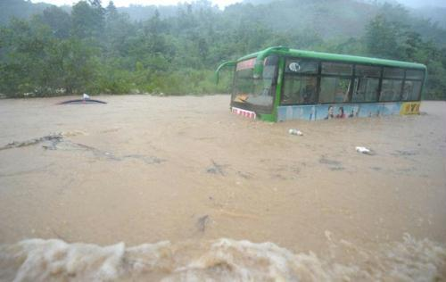 A bus is trapped on a flooded street in Chizhou, east China's Anhui Province, July 13, 2010.(Xinhua/Guo Chen)