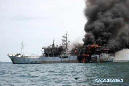 A fishing boat with eight fishermen on board catches fire about 15 nautical miles away from Port Dickson in the Malacca Straits, July 15, 2010. Two Chinese and six Filipinos, aged between 25 and 55, were on board the ship registered in southeast China's Taiwan when the incident took place due possibly to engine breakdown. The eight victims have received medical treatment on the cruise ship and they did not suffer from severe injuries. (Xinhua)