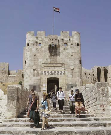 Tourists walk down the steps of the entrance of the Citadel of Aleppo in northern Syria in this June 23, 2010 file photo. Subtlety is the hallmark of Aleppo, one of the world's richest historical sites whose inhabitants possess a quiet pride and a cosmopolitan culture that has survived Mongol destruction and steady economic decline.(Xinhua/Reuters Photo)