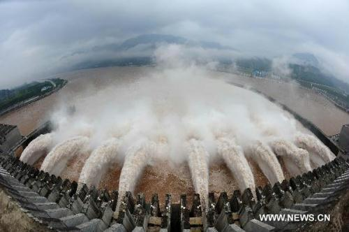 Flood waters are sluiced with the water outflux monitored at 40,000 cubic meters per second at Three Gorges Dam in Yichang, central China's Hubei Province, July 20, 2010. China's Three Gorges Dam project on the Yangtze River stood its biggest flood-control test at 8 a.m. Tuesday since completion, as the flow on the river's upper reaches topped 70,000 cubic meters a second. All ferry services were halted at the Three Gorges Dam on Monday, and would be resumed after the influx decreased to 45,000 cubic meters per second.(Xinhua Filephoto)