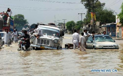 PeoplepushvehiclesthroughthewaterloggedstreetinnorthwestPakistan'sRisalpuronAugust2,2010.(Xinhua/UmarQayyum)