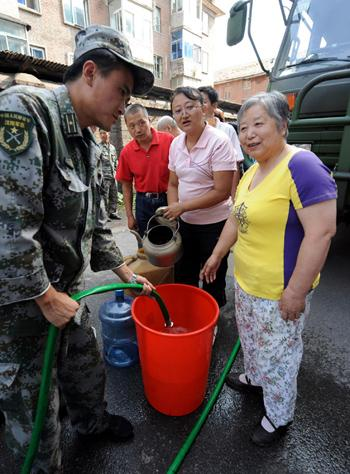 Residents wait for drinking water in Tonghua, Jilin province August 2. Torrential rain has damaged water pipelines in the city, leaving 330,000 people without tap water. To relief the water shortage, fire trucks and temporary water supply stations provide water to residential communities in the city every day. [Photo/Xinhua]