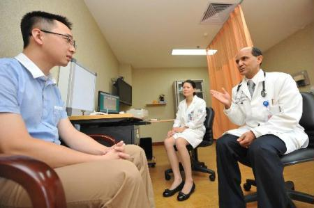Pokhrel(L), an American general medical practitioner, talks to his patient in Sir Run Run Shaw Hospital in Hangzhou, east China's Zhejiang Province, Aug. 3, 2010. Pokhrel has more than 20 years experience as general medical practitioner, he will work for two months in China to train Chinese medical doctors. (Xinhua/Wang Dingchang)