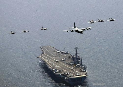 "A U.S. Marine Corps C-130 Hercules aircraft leads a formation of F/A-18C Hornet strike fighters and A/V-8B Harrier jets over the aircraft carrier USS George Washington (CVN 73) in the East Sea of Korea, July 27, 2010. The Republic of Korea and the United States are conducting the combined alliance maritime and air readiness exercise ""Invincible Spirit"" in the seas east of the Korean peninsula from July 25 - 28, 2010. This is the first in a series of joint military exercises that will occur over the coming months in the East and West Seas.(Xinhua/Reuters)"