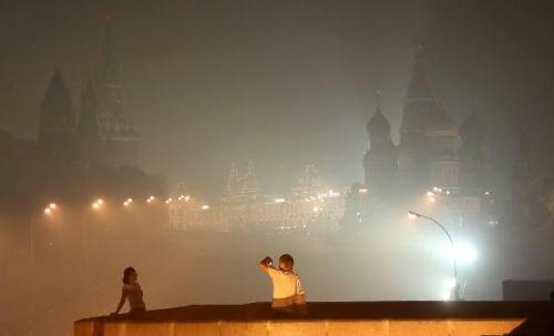 People walk on the Red Square among thick smog in Moscow, capital of Russia, Aug. 4, 2010. Moscow suffered serious air pollution due to the forest and peat fires. (Xinhua/Lu Jinbo)