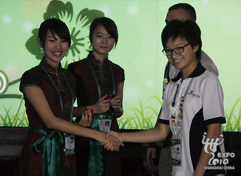 Staff members of the USA Pavilion and China's Joint Provincial Pavilion exchange gifts.