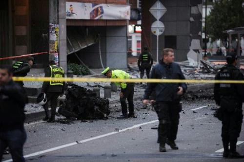 Police officers investigate at the scene of a car bomb explosion in Bogota August 12, 2010. A suspected car bomb exploded on Thursday in the north of Colombia's capital Bogota outside a main radio station, slightly injuring 9 people and blowing out windows in a rare urban attack.(Xinhua/AFP Photo)