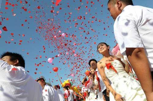 "Newlyweds attend the ceremony during a group wedding in Pingdingshan, central China's Henan Province, Aug. 16, 2010. A total of 77 newlyweds took part in the mass wedding on ""Qixi"" festival which falls on Chinese lunar July 7 and is regarded as the Chinese Valentine's Day. (Xinhua/Zhao Peng)"