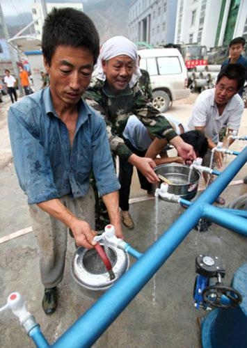 Local people get drinking water from a newly-dug well in Zhouqu county on Monday. (Photo: China Daily)