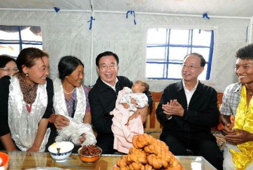 He Guoqiang (C), a member of the Standing Committee of the Political Bureau of the Central Committee of the Communist Party of China (CPC) and chief of the CPC Central Commission for Discipline Inspection, visits the family of a villager of the Tibetan ethnic group in Jiegu Township of Yushu County, northwest China's Qinghai Province, Aug. 17, 2010. (Xinhua/Li Tao)