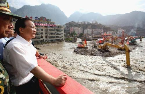 Chinese Premier Wen Jiabao stands on the Chengjiang Bridge to inspect floodwater of the barrier lake as machines dredge the channel of the Bailongjiang River in landslide-hit Zhouqu County, Gannan Tibetan Autonomous Prefecture in northwest China's Gansu Province, Aug. 22, 2010. Wen made an inspection tour in Zhouqu on Aug. 21-22.(Xinhua/Yao Dawei)
