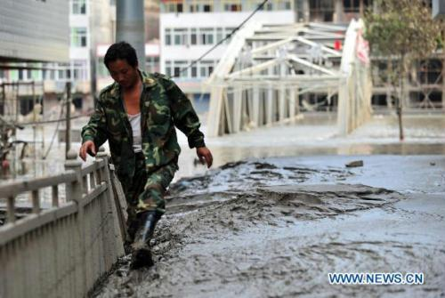 A local resident walks in the mud after the flood retreated in mudslide-hit Zhouqu, northwest China's Gansu Province, Aug. 28, 2010. Rescuers continued the cleaning work at the blocked part of the Bailong River in Zhouqu so that the reserved water could be discharged as soon as possible. Since Aug. 8, more than 400 heavy machine have been deployed in Zhouqu to work almost around the clock to clean the mud at the watercourse. (Xinhua/Liang Qiang)