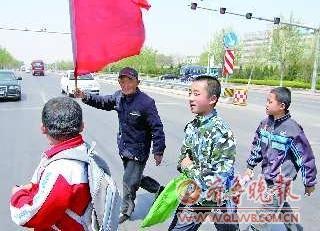 �T谄牒酉�308国道路口,张光城17年如一日地护送孩子们上下学。
