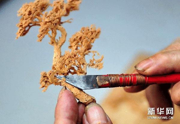 吴学宝在手工雕刻软木画松树配件