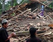 居民站在一座倒塌的房屋旁