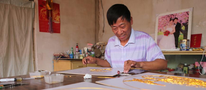 拥有造型艺术和服装设计双学位的王刚,此前曾为当村官不能发挥自己的特长而有些惋惜,我一直希望寻找一个切入口,能把特长和村官的工作结合在一起。经过考察,他确定了金丝岩彩画,把宿舍作为试验基地,开始了创业。王刚和另外两名村官一起开始了金丝岩彩画的制作,并培训一些在家赋闲的村民参与掐丝制作,按件付给村民加工费。    2012年6月9日中午,记者和王刚走进村民张淑俊家。此行给张淑俊带来3块用蓝色圆珠笔描摹好金丝岩彩画的奥松板,让她在底板上嵌丝。    会十字绣的张淑俊是王刚教出来的第一个村民,她又带会了村
