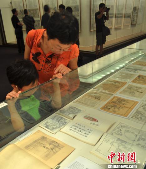 观众在观赏《红楼梦》画册展览。