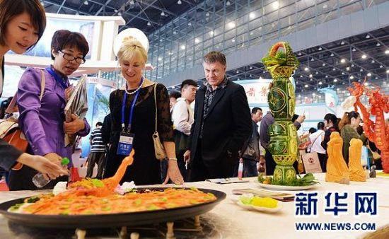 """9月27日,与会的国内外代表在展会上参观。当日,世界旅游城市博览会在郑州国际会展中心开幕。此次博览会以""""旅游·城市活力之源""""为主题,通过城市特色旅游产品和旅游商品展示,精彩呈现各地旅游资源,开展多种形式的旅游推介与合作。"""