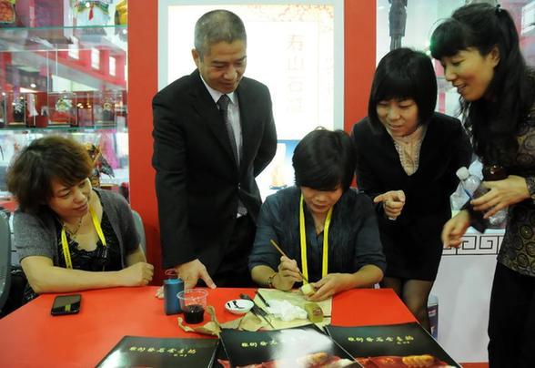 10月26日,福建翰墨金石艺术馆寿山石文化艺术研究院的福建省工艺美术大师叶子(右三)在向参观者讲解寿山石巧色雕刻。