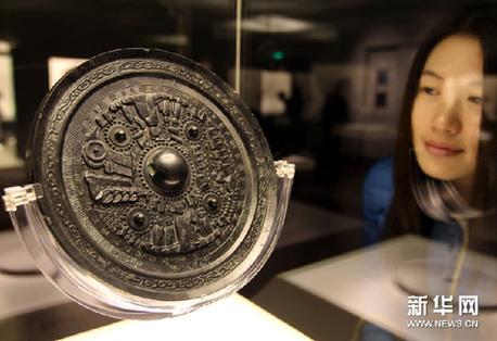 """11月15日,一名观众在欣赏东汉""""石氏车马人物画像镜""""。新华网图片 任珑 摄"""