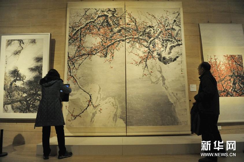 11月18日,观众在中国美术馆欣赏展出的关山月绘画作品《飞雪迎春到》(中)。