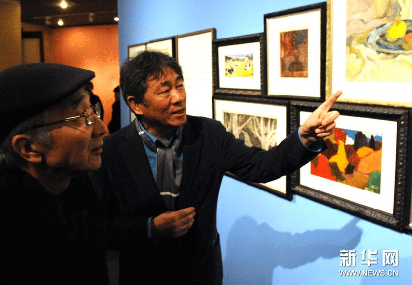 12月7日,谭平(右)在介绍自己的绘画作品。