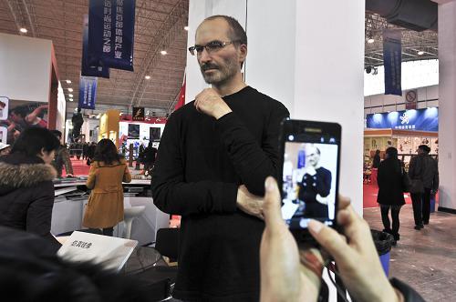 12月20日,一名参观者在第七届中国北京国际文化创意产业博览会上拍摄高仿硅像《乔布斯》。新华社发(王振 摄)