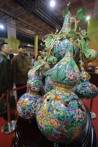 12月20日,在第七届中国北京国际文化创意产业博览会上,观众在欣赏景泰蓝作品《福禄万代》。新华社发(王振 摄)