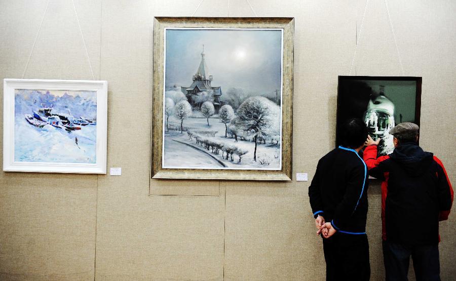 (2)1月9日,两位市民在欣赏冰雪风景油画作品
