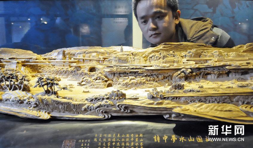 2月5日,市民在沉香木雕预展会上欣赏郑春辉的木雕作品。