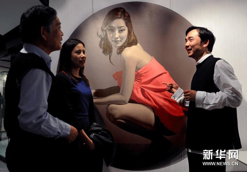 3月7日,艺术家侯庆(右)向观众介绍自己的绘画作品。