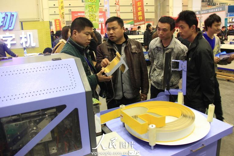 """3月19日,参观者在郑州国际会展中心举行的""""2013春季中国郑州第22届中原广告展""""上参观印刷设备。"""
