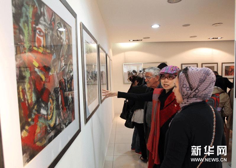 来自中华文化发展促进会的画家许琪萍(中)向参观者讲解画作。