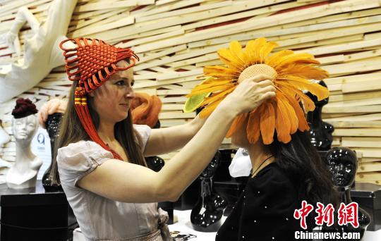 图为伊丽莎白-考奇为参观者试戴帽子。蒋振江 摄