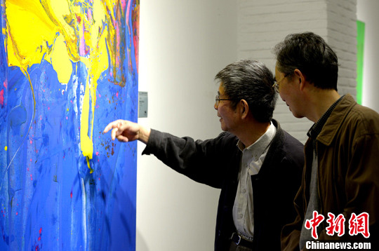两名艺术家正在讨论作画手法。李一芳 摄