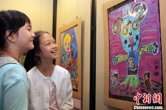 """5月19日,以""""变形记""""为主题的海峡两岸少儿美术大展在台北艺术教育馆开幕。图为台北少年在观赏同龄人的作品《小老鼠变形记》。中新社发 刘舒凌 摄"""