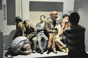 """5月20日,""""与时代同行——中国美术馆建馆50周年藏品大展""""在北京中国美术馆开幕。本次展览共展出作品660余件,内容涵盖国画、油画、雕塑、版画等多个门类。展览依托中国美术馆藏精品,在以往学术研究和展览陈列的基础上,进一步对藏品进行梳理,通过""""传承与引进""""""""苦难与抗争""""""""探求与拓进""""""""主人与家园""""""""反思与开放""""""""多样与繁荣""""六个部分,展现了一百多年来中国美术波澜壮阔的历史发展进程。图为一名观众在中国美术馆参观拍摄展出雕塑作品《13号线•2011》。新华社记者 鲁鹏 摄"""